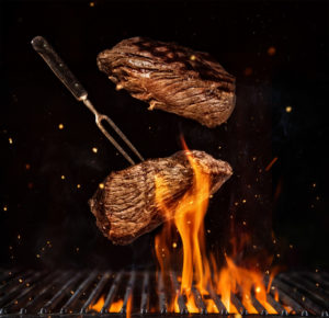 Flying beef steaks over flaming grill grid, isolated on black background. Barbecue and cooking